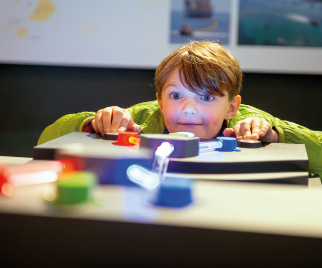 Young boy playing with gadgets in Porthcurno Telegraph Museum exhibition