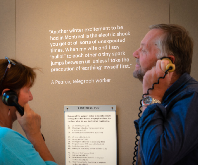 Man and woman holding telephones at Porthcurno Telgraph Museum exhibition