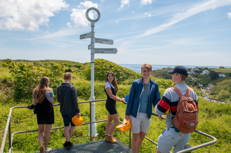 Group of people stand by signage on the Cornish coast
